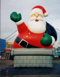 giant santa coming out of chimney advertising inflatable
